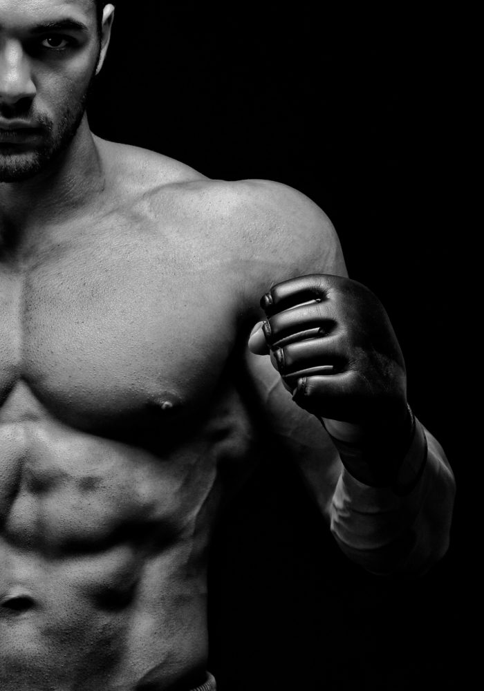 Powerful shirtless male boxer posing in front of black background