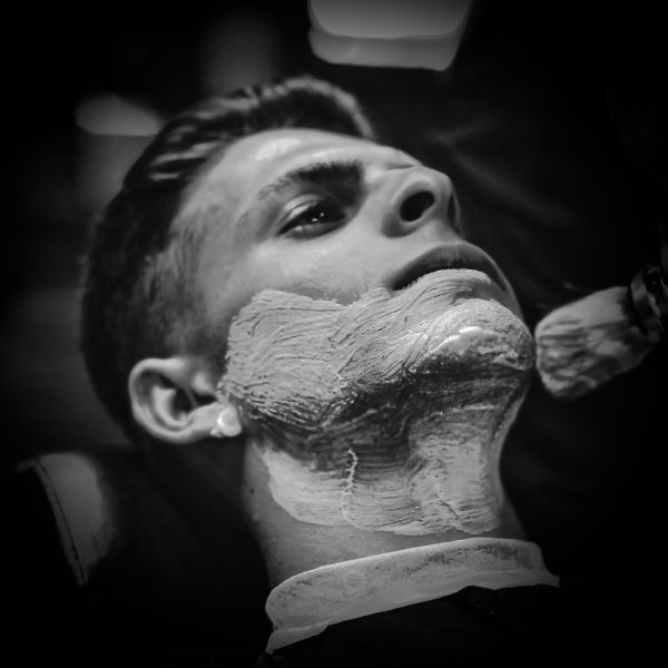 Crop stylish applying foam on customer's cheeks for shaving while working in barbershop.